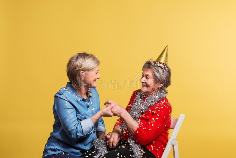 Portrait of a senior women in studio on a yellow background. Party concept. stock images