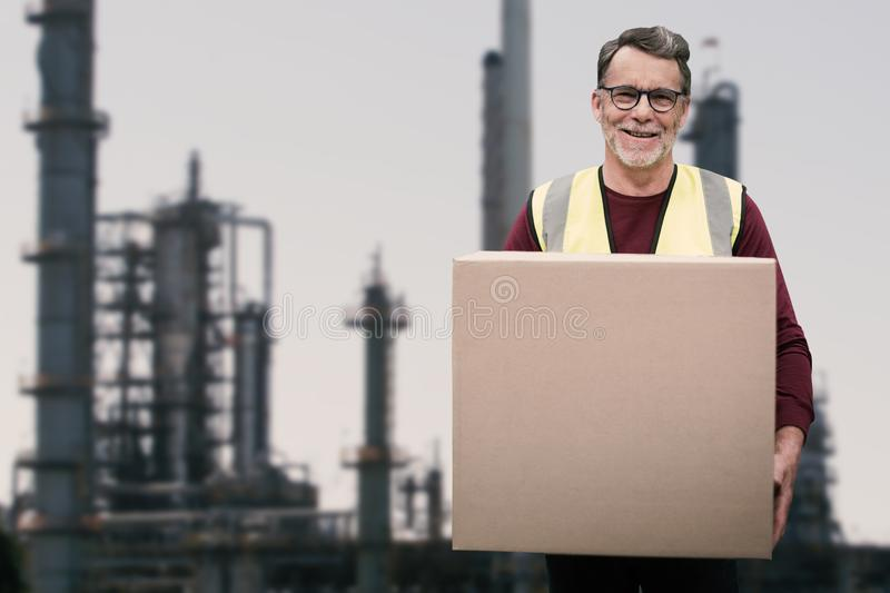 Composite image of portrait of senior worker holding cardboard box. Portrait of senior worker holding cardboard box against factory and industry stock photography