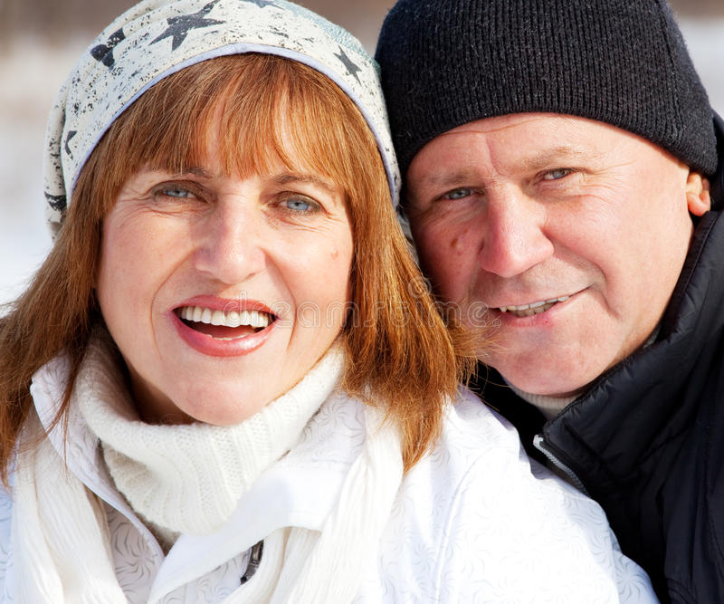 Portrait seniors couple in winter park. Happy seniors couple in winter park. Elderly mature people stock photos