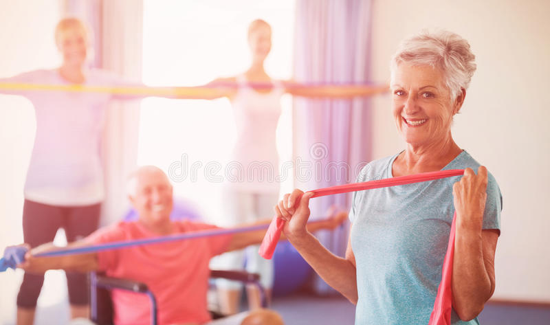 Portrait of seniors exercising with stretching bands. During sports class stock image
