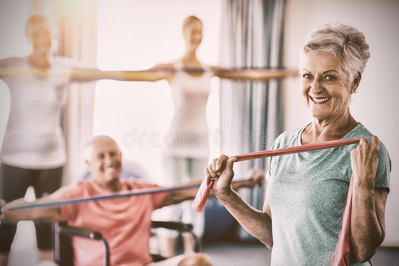 Portrait of seniors exercising with stretching bands. During sports class royalty free stock photography