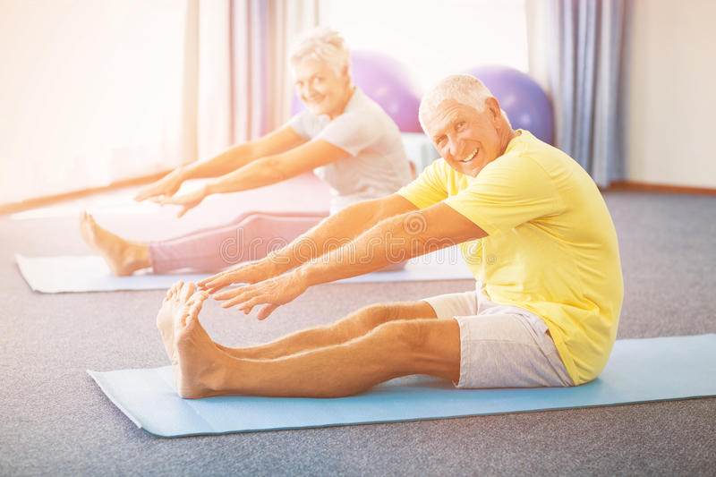 Portrait of seniors stretching legs. In studio royalty free stock photo