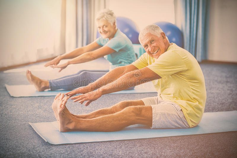 Portrait of seniors stretching legs. In studio stock photography