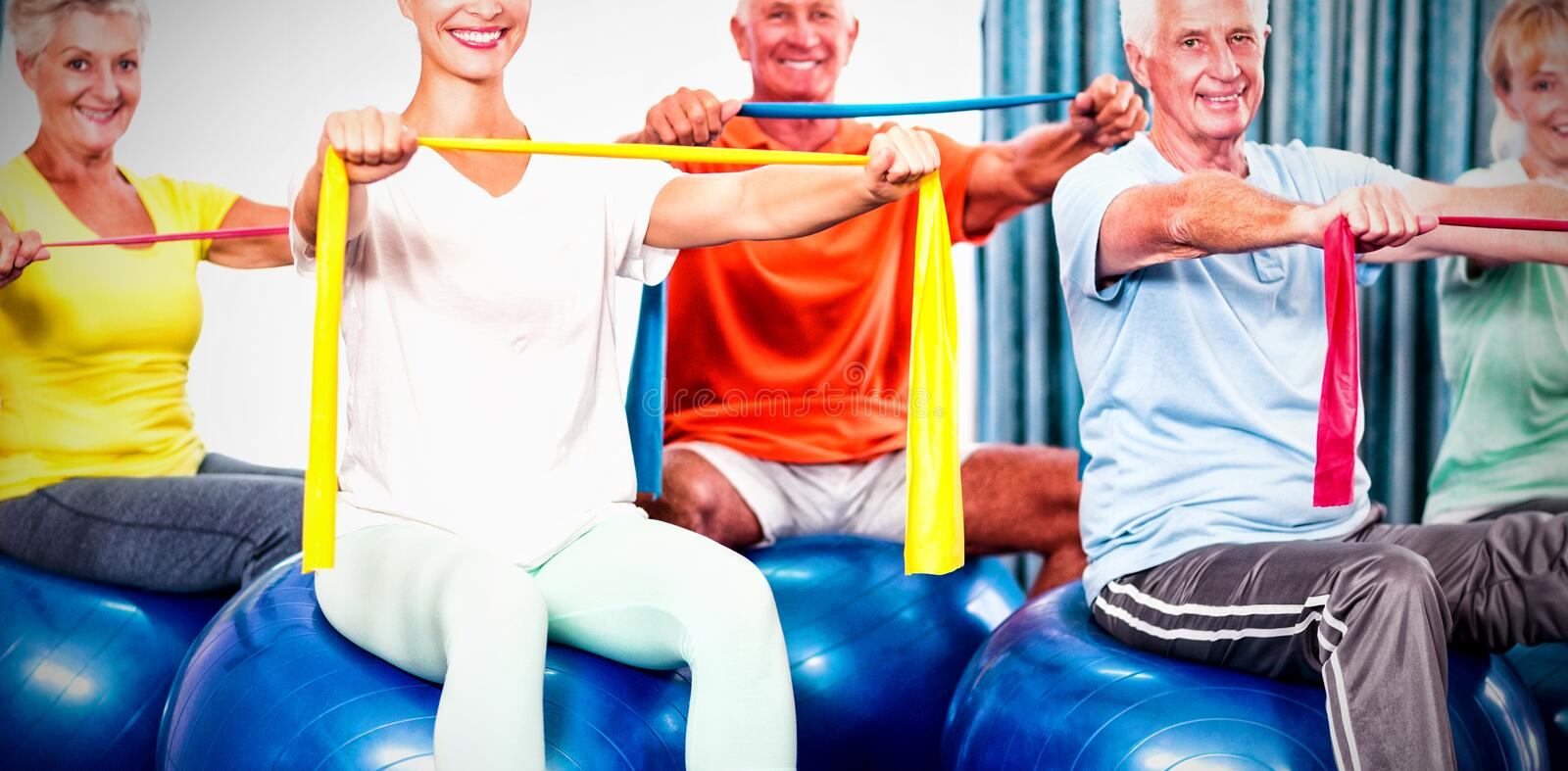 Portrait of seniors using exercise ball and stretching bands. During sports class stock photo