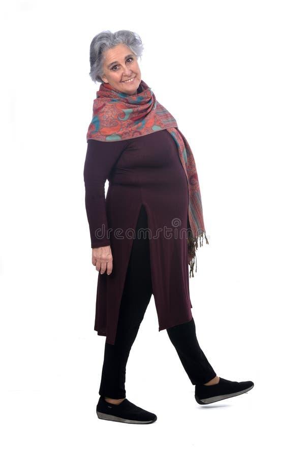 Portrait of a senir woman walking on white stock photography