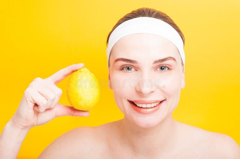 Portrait of sensitive woman holding lemon near face stock images