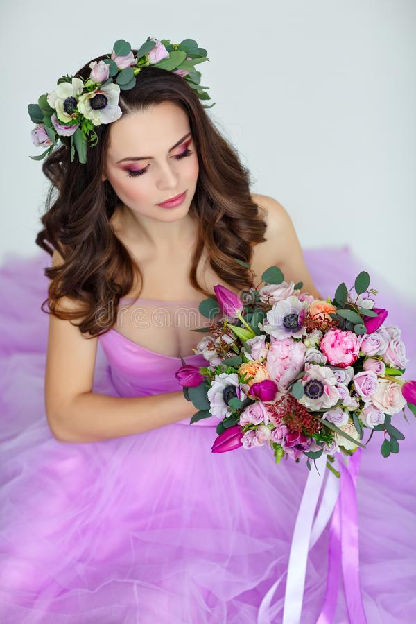 Portrait of sensual beautiful brunette girl in purple dress, wreath and bouquet of flowers. Beauty. White background, Her eyes ar stock photos
