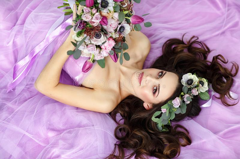 Portrait of sensual beautiful brunette girl in purple dress, wreath and bouquet of flowers lying on her back. Beauty stock photos
