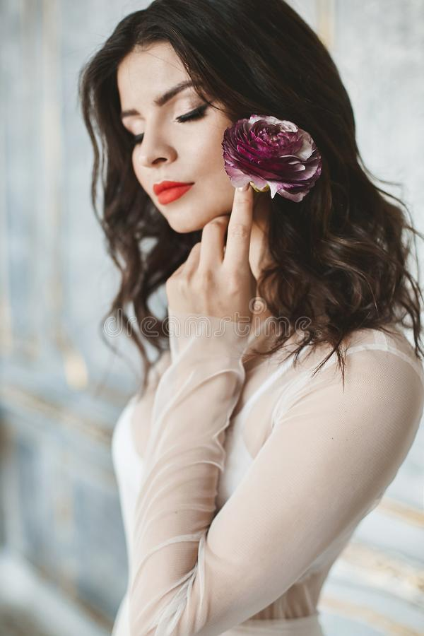 Portrait of sensual and beautiful brunette model girl with bright makeup and closed eyes in stylish light peignoir with flower in royalty free stock photography