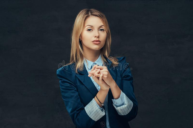 Portrait of a sensual blonde business woman dressed in a formal suit and blue shirt, posing in a studio. on a stock images