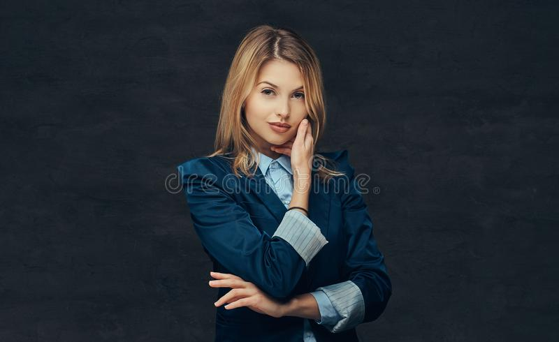 Portrait of a sensual blonde business woman dressed in a formal suit and blue shirt, posing in a studio. on a royalty free stock photography