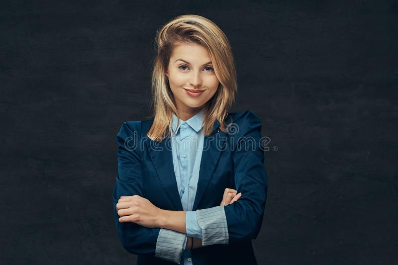 Portrait of a sensual blonde business woman dressed in a formal suit and blue shirt, posing in a studio. on a royalty free stock photo