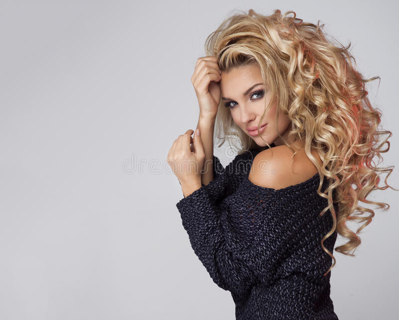 Portrait of sensual blonde woman. Portrait of beautiful smiling blonde woman with curly long hair stock image