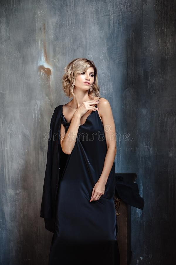 Portrait of sensual blonde woman in a long silk evening dress, fashion beauty photo in interior royalty free stock photo