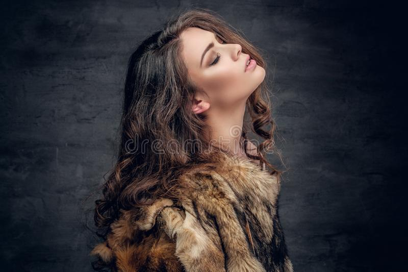 Sensual brunette female dressed in a fur coat. stock image