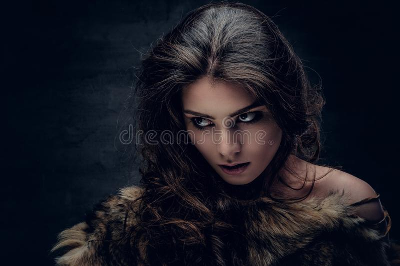 Sensual brunette female dressed in a fur coat. royalty free stock photos