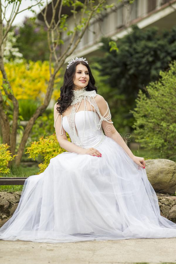 Portrait of Sensual Caucasian Bride With Diadem Sitting In Flowers Garden Outdoors. Wearing Beads Necklace. Vertical Shot royalty free stock photo