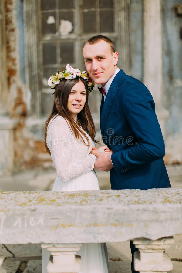 Portrait of sensual just married husband and wife hugging posing in antique ruined palace.  royalty free stock image