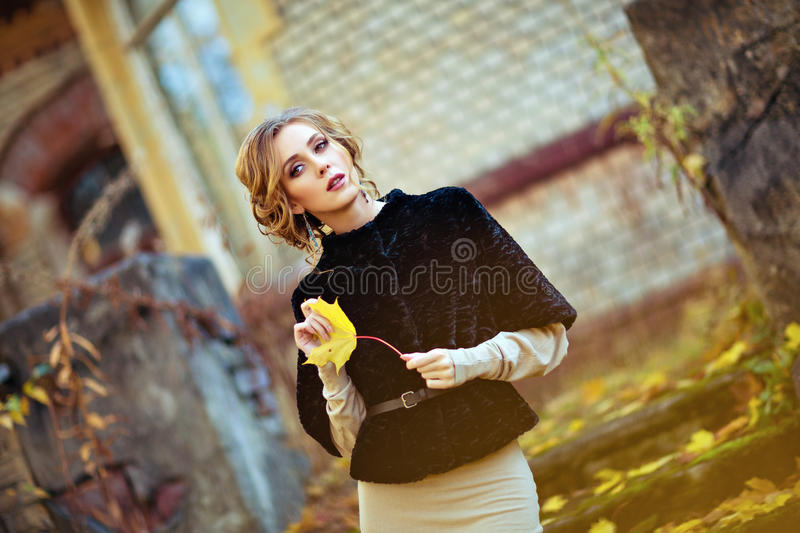 Portrait of a sensual kinky girl in the black coat with the sheet in his hands fall stock photo
