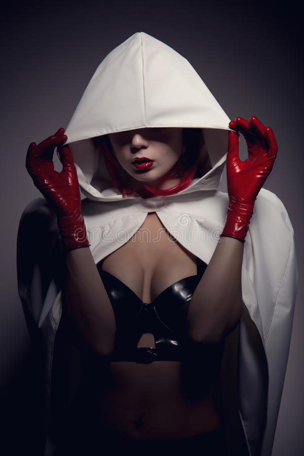 Portrait of sensual vampire girl with red lips. Wearing white hooded jacket, artistic shot royalty free stock photography