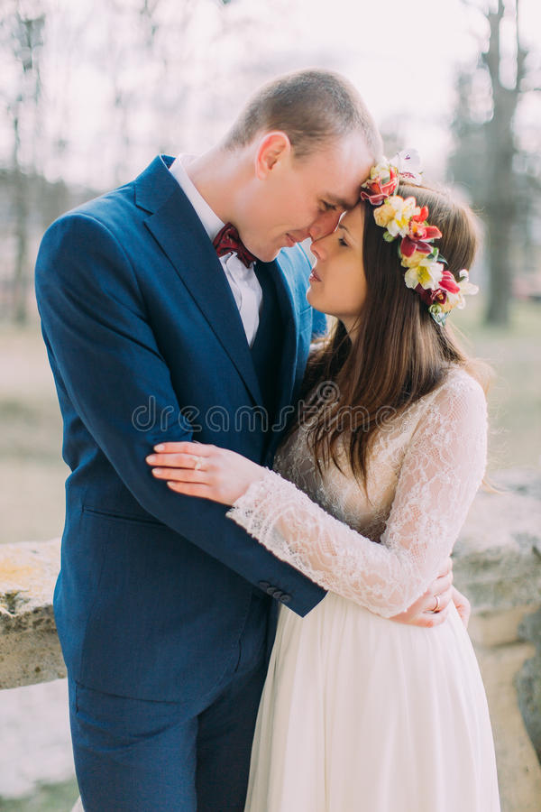 Portrait of sensual wedding couple embracing. Beautiful young bride embraces with handsome groom outdoor stock photography