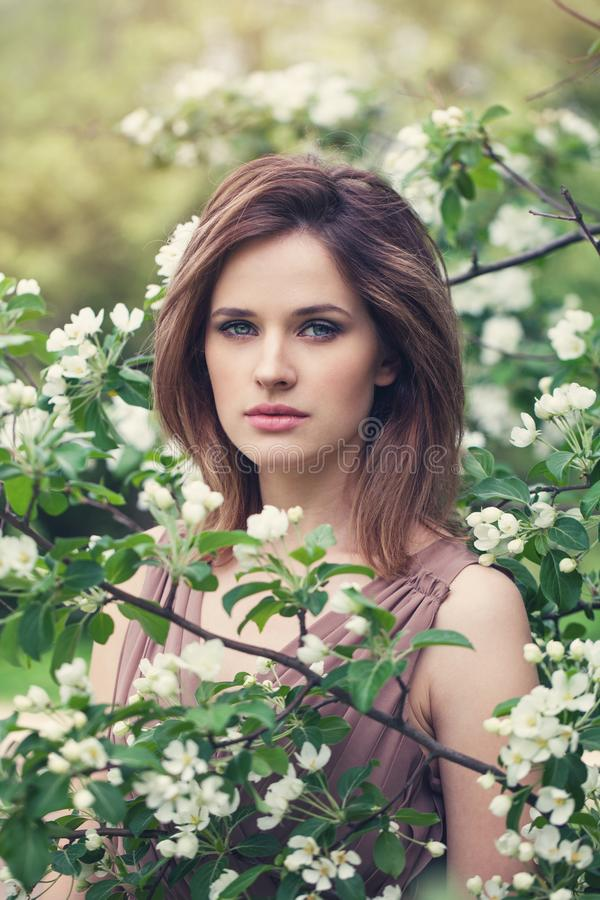 Portrait of sensual woman in spring blossom garden. Natural beauty stock photo