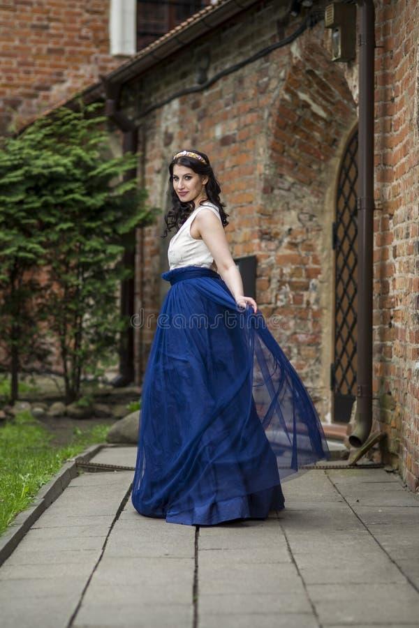 Portrait of Sensual Young Brunette Lady Dancing in Long Blue Dress. Wearing Tiara. Vertical Shot stock photos