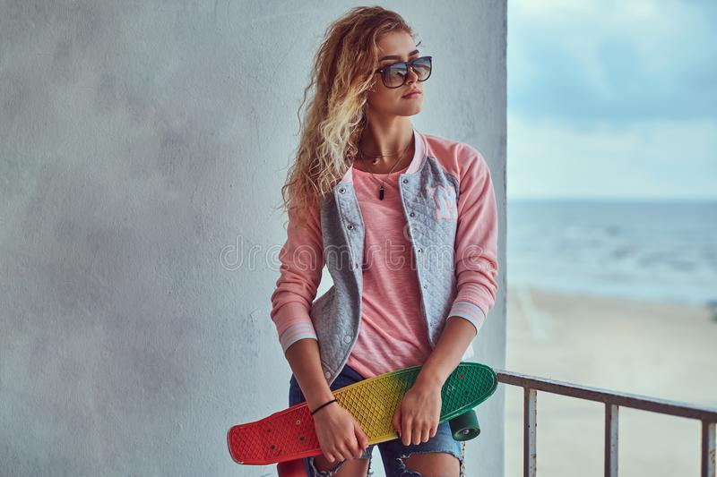 Portrait of a sensual young girl with blonde hair in sunglasses dressed in a pink jacket standing near a guardrail royalty free stock photo