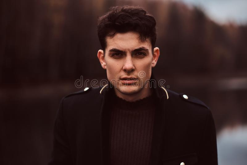 Portrait of a sensual young man wearing a black coat in the autumn forest. stock photography
