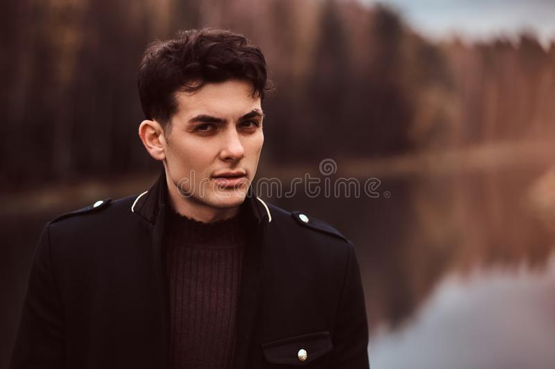 Portrait of a sensual young man wearing a black coat in the autumn forest. royalty free stock images