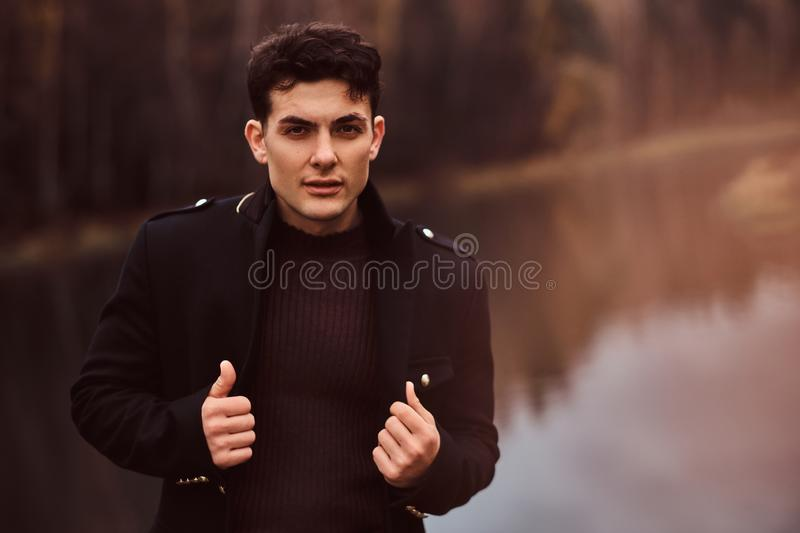 Portrait of a sensual young man wearing a black coat in the autumn forest. stock photo