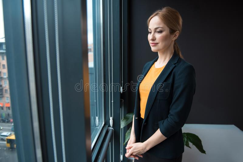 Serious girl situating in office stock photo