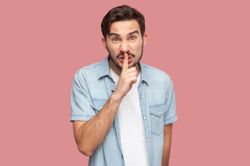 Portrait of serious or angry bearded young man in blue casual style shirt standing with silence sign gesture, finger on lips and. Looking at camera. indoor royalty free stock image