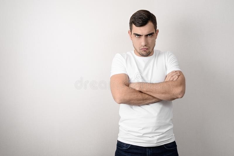 Portrait of a serious, angry young man with folded arms in a white t-shirt with a copy of space. Portrait of serious, angry young man with folded arms in white t stock images