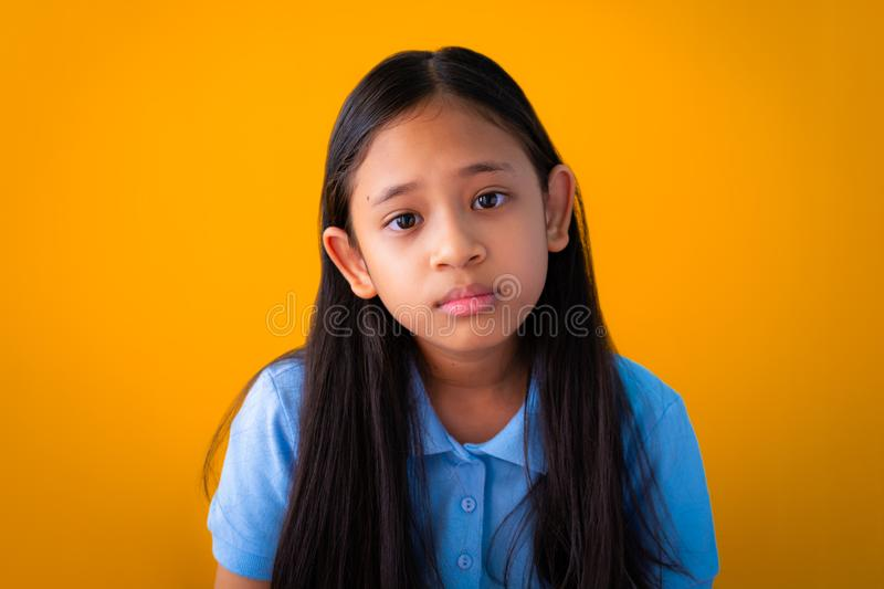 Portrait of serious asian cute girl  orange background stock photo