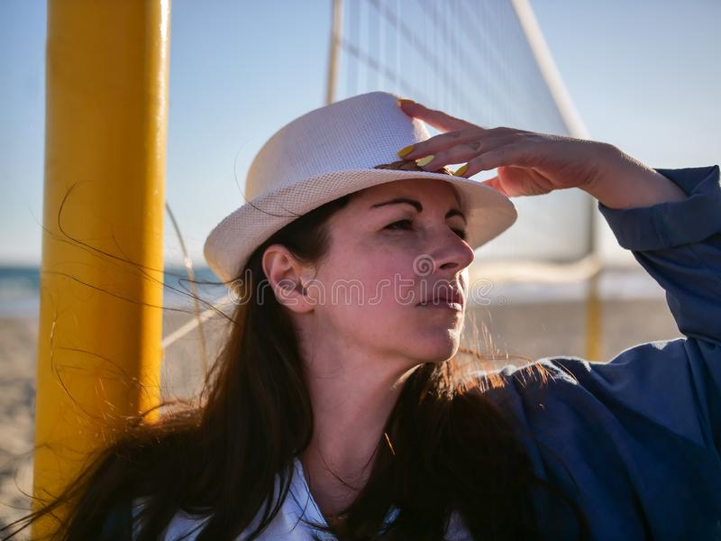 Portrait of a serious attractive brunette girl in a white hat, looks away stock image
