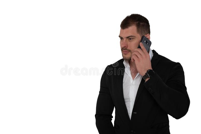 Beautiful serious business man in suit with smartphone on white background royalty free stock photos