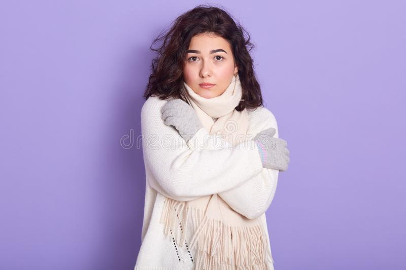 Portrait of serious attractive female with curly black hair looking directly at camera, crossing arms, wearing white sweater, stock images