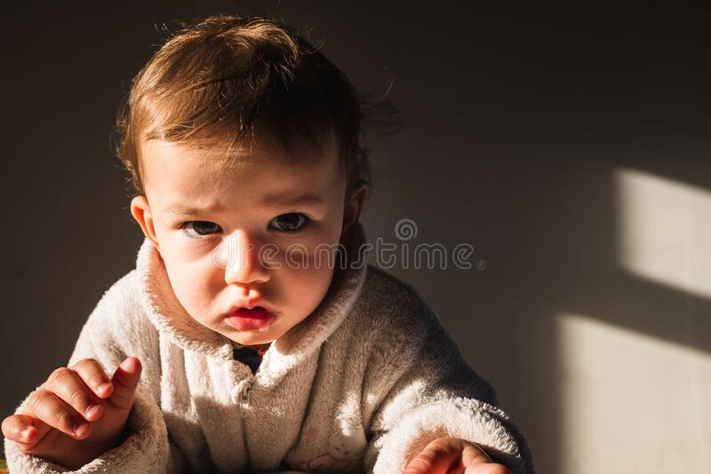 Portrait of serious baby isolated with dark background.  stock photos