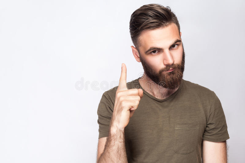 Portrait of serious bearded man with warning finger and dark green t shirt against light gray background. stock photos
