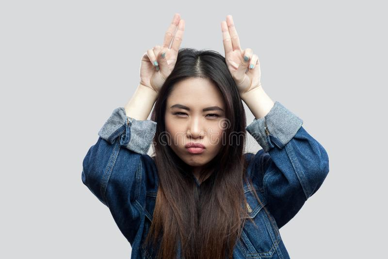 Portrait of serious beautiful brunette asian young woman in casual blue denim jacket with makeup standing with horns and looking. At camera. indoor studio shot royalty free stock photos