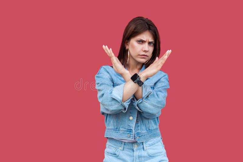 Portrait of serious beautiful brunette young woman with makeup in denim casual style standing and looking at camera with x sign. Hand gesture. indoor studio stock photo