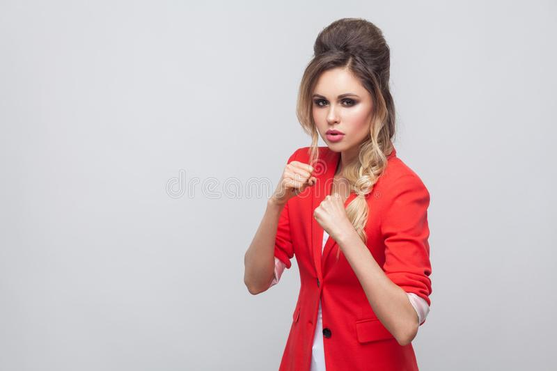 Portrait of serious beautiful business lady with hairstyle and makeup in red fancy blazer, standing in attack boxing pose and. Looking at camera. indoor studio royalty free stock image