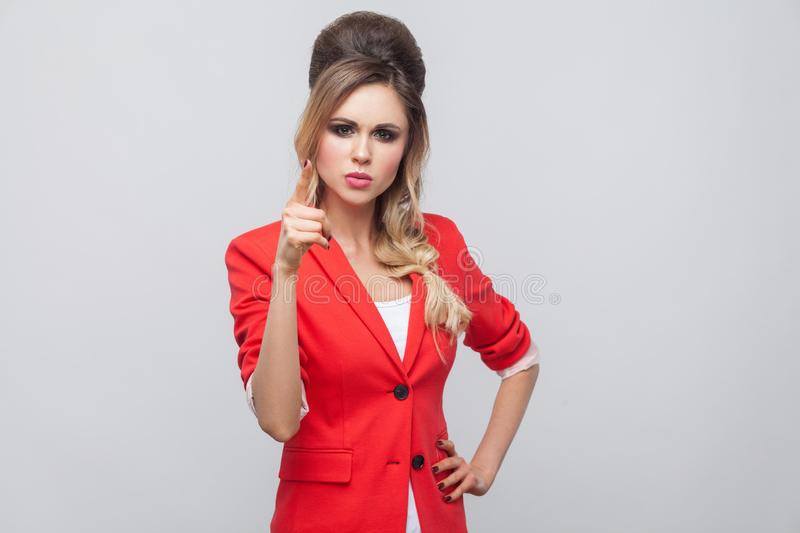 Portrait of serious beautiful business lady with hairstyle and makeup in red fancy blazer, standing with hand on waist and alarm. Sign looking at camera. studio stock photos