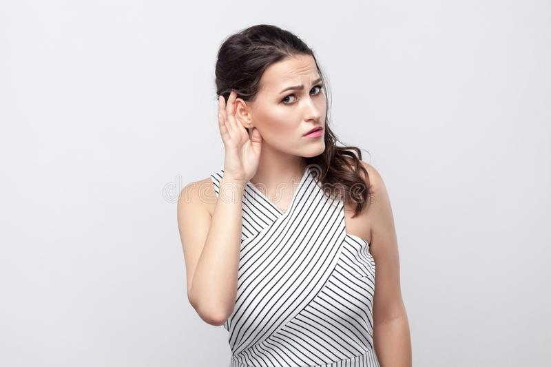 Portrait of serious beautiful young brunette woman with makeup and striped dress standing, holding hand near ear, looking at royalty free stock photo