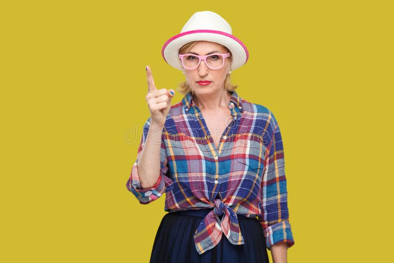 Portrait of serious bossy modern stylish mature woman in casual style with hat and eyeglasses standing with warn sign and looking. At camera. indoor studio shot stock images