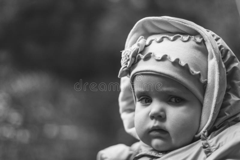 Portrait of serious brooding eleven month old baby girl on natural background with copy space royalty free stock photos