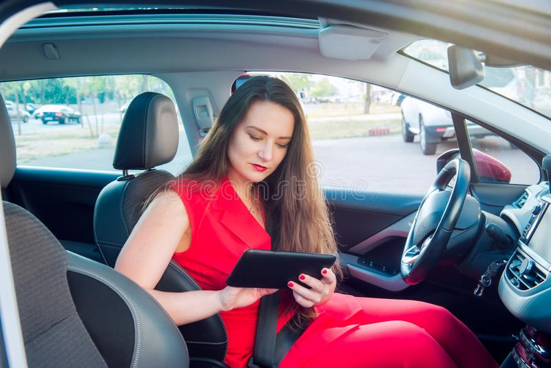 Portrait of serious business lady, caucasian young woman driver in red summer suit setting up the route on a navigator while royalty free stock photography