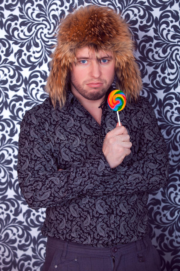 Portrait of serious business man in black shirt with patterns in a fur hat. With lollipop royalty free stock photography