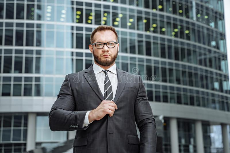Portrait of a serious business man in a suit and glasses on the background of an office building stock photography